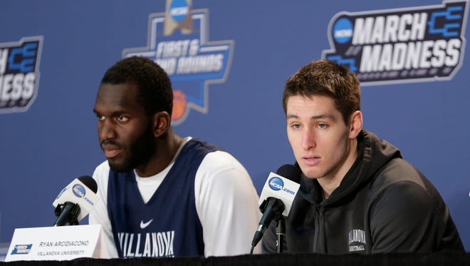Villanova's Ryan Arcidiacono responds to questions as teammate Daniel Ochefu listens during a news conference before a second-round men's college basketball game against Iowa in the NCAA Tournament, Saturday, March 19, 2016, in New York. (AP Photo/Frank Franklin II)