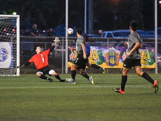 All-Island Second team's Jason Kim, center wearing grey uniform, gets the ball pass the All-Island First team's goalie to score during the first-ever Independent Interscholastic Athletic Association of Guam's All-Island All Star boys' soccer matchup at the Guam Football Association National Training Center in Dededo on Wednesday, Dec. 21, 2016. In the end, the Second team was victorious with a final score of 2 - 4.