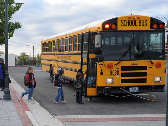 Children board a school bus to Libby Booth Elementary School.