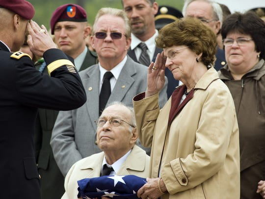 Trudy and Sal Corma are saluted by Lt. Gen. Frank Helmick during the funeral of their son in 2010.