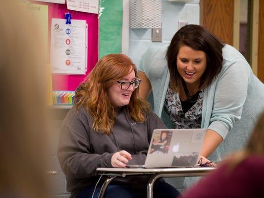 Mount Vernon High School English teacher Katie Bushard helps sophomore Lauren Bryant, 15, during class recently.