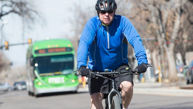 A cyclist is followed by a MAX bus as they move southbound on Mason Street Friday, March 11, 2016.