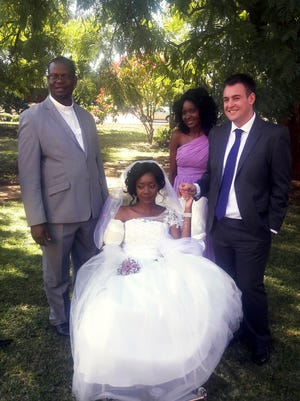 """In this photo taken on Saturday, May, 5, 2018, Zanele Ndlovu, centre, and Jamie Fox hold hands on their wedding day at a hospital Chapel in Bulawayo, Zimbabwe. A couple attacked by a crocodile wedded days later in a Zimbabwean hospital, where the bride was recovering after losing an arm. """"In one week we went from shock and agony to a truly amazing experience,"""" 27-year-old Jamie Fox told The Associated Press Monday, May 7. (AP Photo) ORG XMIT: XTM102"""