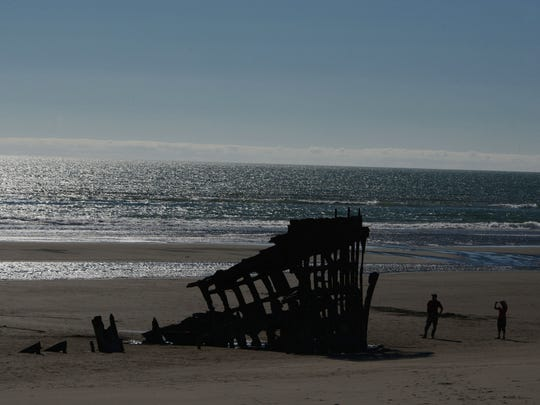 Visitors explore the rusty remains of the century-old shipwreck Peter Iredale along the beach at Fort Stevens State Park near Astoria on Saturday, July 26, 2014.
