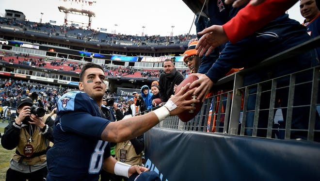 Titans quarterback Marcus Mariota celebrates with fans after beating the Broncos on Sunday.