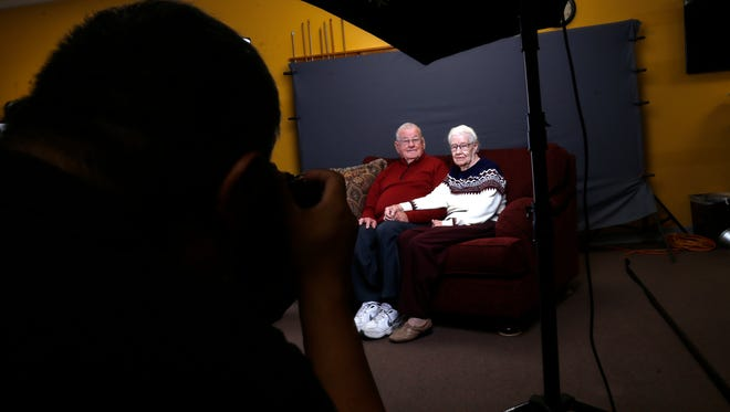Bob and Harriett Foster get their portrait taken by San Juan College intermediate digital photography student Dean Howard Thursday during a portrait project at the Bloomfield Senior Center.