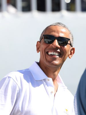 Former president Barack Obama flashes a smile during the first round foursomes match of The President's Cup golf tournament in September