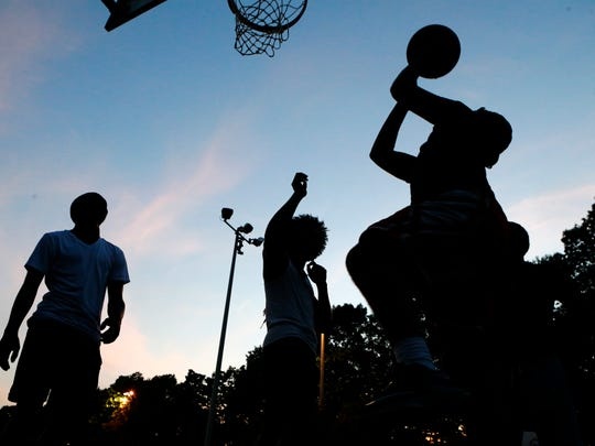 Teens play basketball in the fading light before 9
