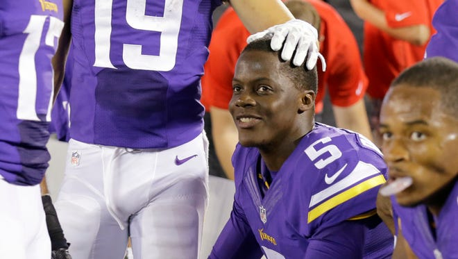 Minnesota Vikings quarterback Teddy Bridgewater is congratulated by a teammate as he sits on the bench during the final seconds of an NFL preseason football game against the Arizona Cardinals, Saturday, Aug. 16, 2014, in Minneapolis. The Vikings won 30-28.