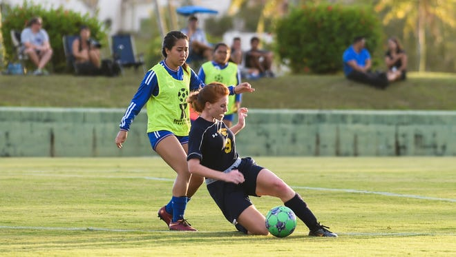 In this file photo, Guam High's Alexandra Perkins (9) dives for the ball against Notre Dame's Amara Gumataotao (5) during an Independent Interscholastic Athletic Association of Guam Girls' Soccer League match.