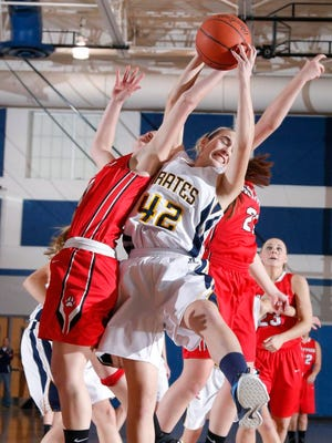 Pewamo-Westphalia's Kenzie Hengesbach (42) and Laingsburg's Nicky McAvoy, left, and Sophie Wilsey, right, fight for a rebound Monday, March 2, in Bath. Laingsburg won 32-26.