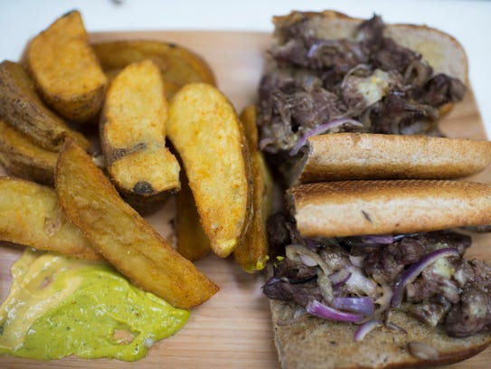 A steak sandwich is served with signature potato wedges