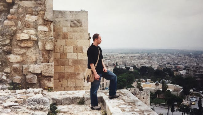Timothy Fitzgerald looks out from a stone ledge atop the walls of the Citadel of Aleppo in 2004, a massive, ancient fortification at the center of the city that has been badly damaged during the civil war.