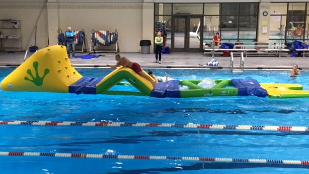 A lifeguard trying out theY's new pool obstacle course.