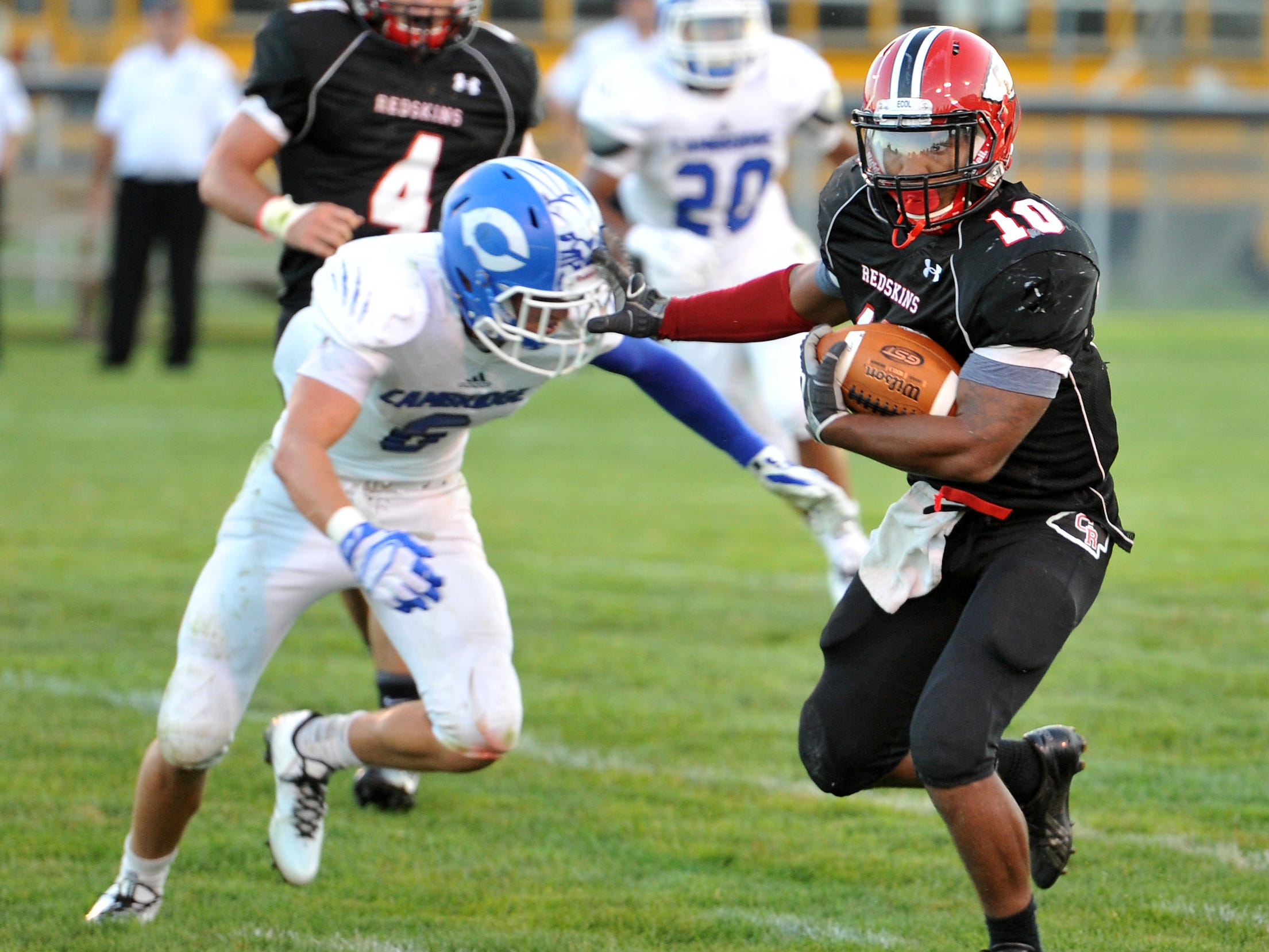 Coshocton Redskins senior Dom Johns stiff arms Cambridge's Riley Hayhurst on his way to the end zone in an Aug. 29 game against Cambridge. Johns was a Division V first-team All-Ohio selection Wednesday.