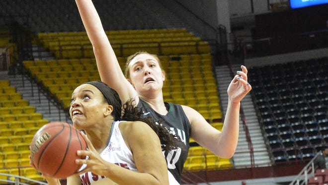 New Mexico State's Tyler Ellis ducks under Eastern New Mexico's Johna McClelland while going up for a layup during Monday night's game at the Pan American Center.