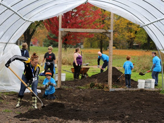Becca Blue (foreground) shovels with a group of volunteers as they take part in Make A Difference Day by getting ready for winter at Riverview Gardens in Appleton, Wis., Saturday, October 24, 2015. The USA Today nationwide event, now in its 24th year, brings out volunteers to help in their communities.
