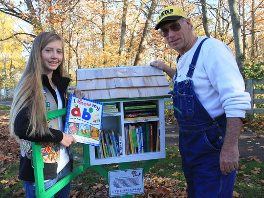Pataskala Girl Scout Edie Bradford recently installed a miniature library at Municipal Park. The Little Free Library works on an honor system. Here, Bradford stocks the library with Pataskala Mayor Mike Compton.