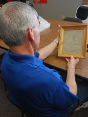 Walter Kronner looks at a plaque made from the rock that sank the steamer Matoa during the Great Storm of 1913.