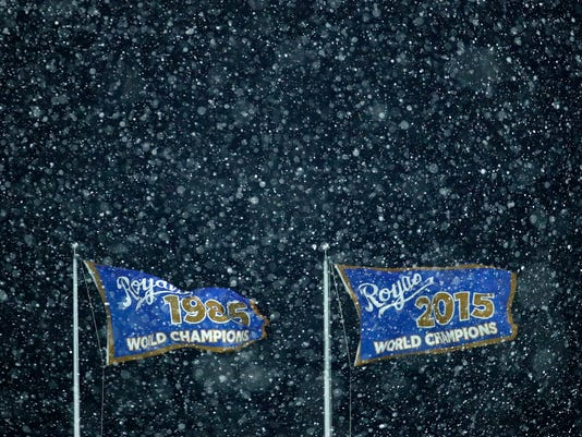 Flags fly as snow falls during the eighth inning of a baseball game between the Kansas City Royals and the Los Angeles Angels, Saturday, April 14, 2018, in Kansas City, Mo. (AP Photo/Charlie Riedel)