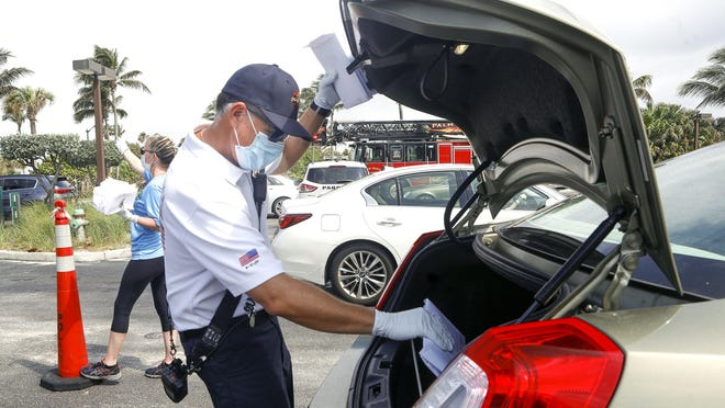 Lt. Joseph Sekula, battalion chief for the Palm Beach fire department, helps to hand out complimentary surgical masks to Palm Beach residents in April.