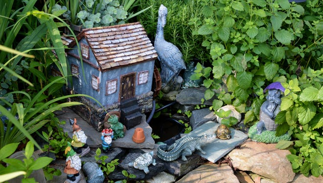 A tiny watermill is tucked among the perennials.
