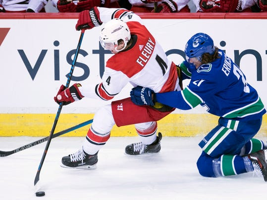 Vancouver Canucks left wing Loui Eriksson (21) competes for control of the puck with Carolina Hurricanes defenseman Haydn Fleury (4) during the third period of an NHL hockey game Tuesday, Dec. 5, 2017, in Vancouver, British Columbia. (Jonathan Hayward/The Canadian Press via AP) - Dundon Signs Purchase Agreement To Buy Carolina Hurricanes