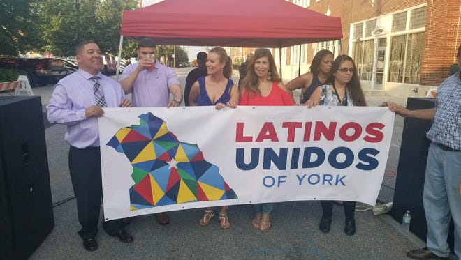 Members of Latinos Unidos of York, a nonprofit organization empowering the local Latino community, unveiled its new logo Friday, June 1, in front of The Parliament Art Gallery and Tea Bar at 116 E. King St. in York City. Logan Hullinger photo
