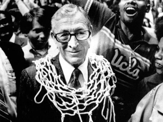 FILE - This March 31, 1975, file photo shows UCLA basketball coach John Wooden wearing a basketball net around his neck after his team won the NCAA basketball championship over Kentucky, 92-85, in San Diego, Calif.  Wooden and George Steinbrenner,  two towering figures in sports, died in 2010, each having transformed his game in a distinct but enduring way.(AP Photo/File)