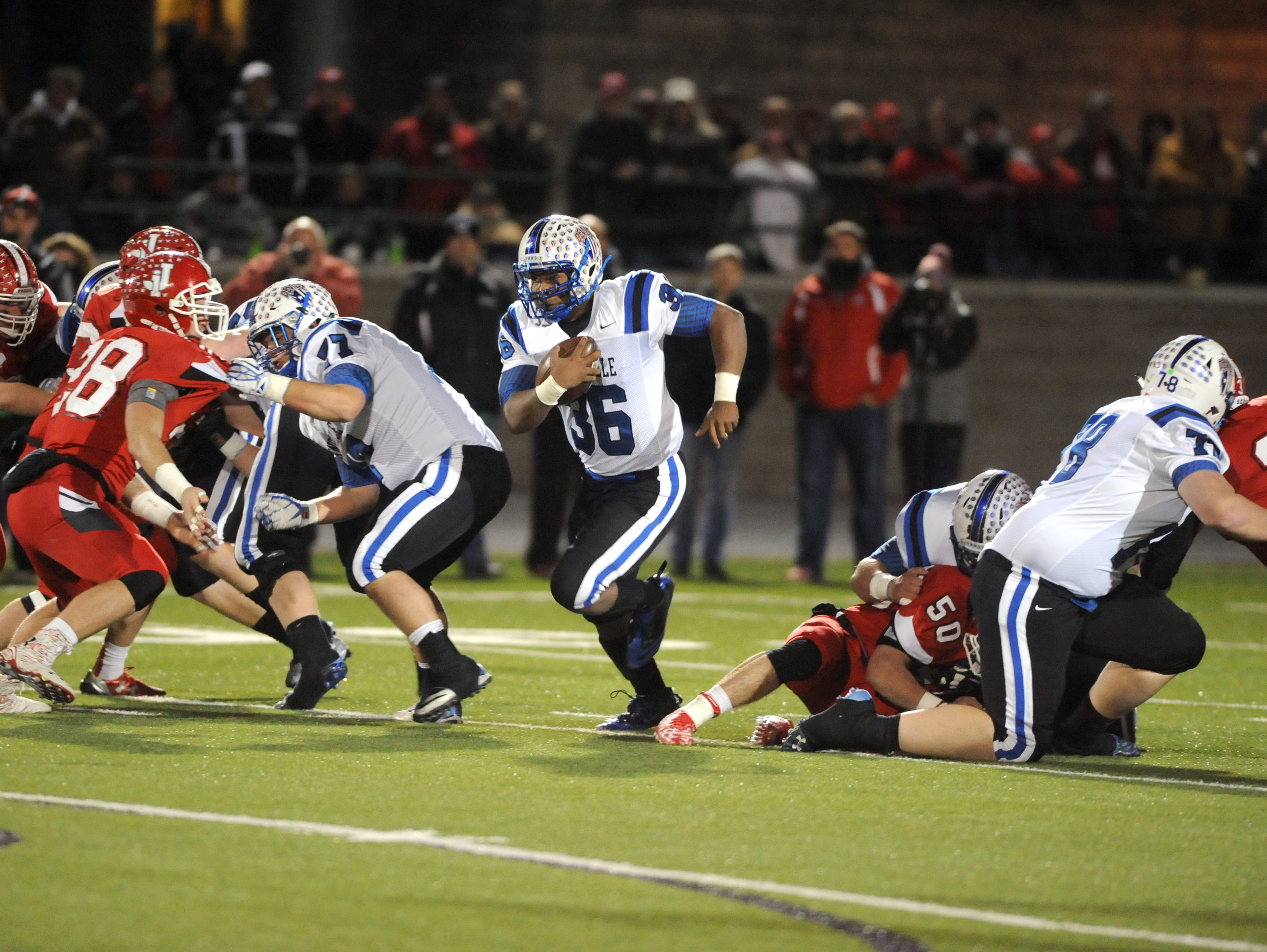 The Zanesville offensive line opens up a hole for Leo Crosby during the Blue Devils victory over Jackson in a Division III regional finals game at Athens High School. The unit, led by Coulter Wilson (right) and Tavian Butts, has helped the Blue Devils amass 4,554 yards this season.