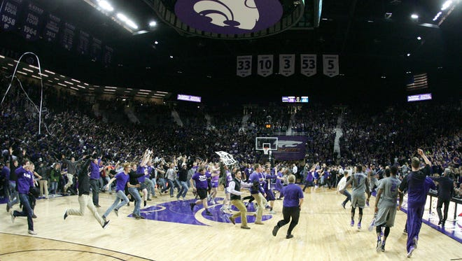 Kansas State fans rush the court Monday night following a 70-63 win against archrival Kansas in Manhattan, Kan.
