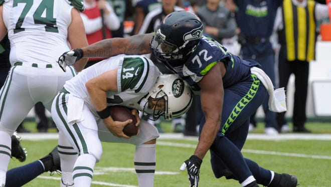 New York Jets quarterback Ryan Fitzpatrick (14) slips away from Seattle Seahawks' Michael Bennett (72) during the first half of an NFL football game Sunday, Oct. 2, 2016, in East Rutherford, N.J.