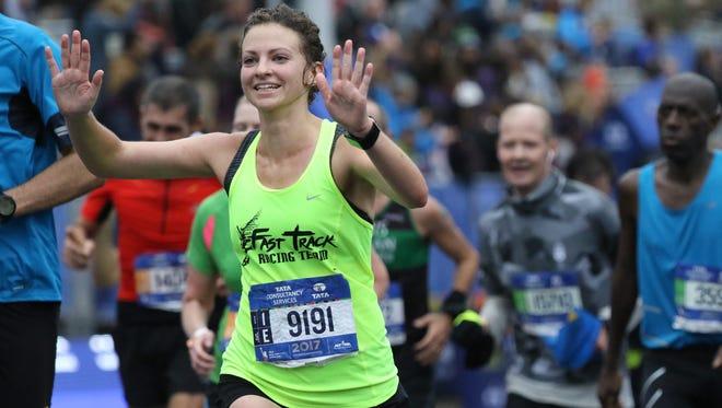 Samantha Clark raises her hands as she crosses the finish line in Central Park, Sunday, November 5, 2017.