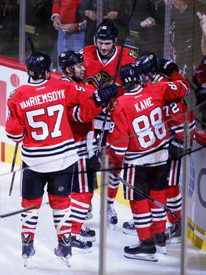 Chicago Blackhawks left wing Artemi Panarin (72) celebrates with teammates after scoring against the New York Islanders during the second period at United Center.