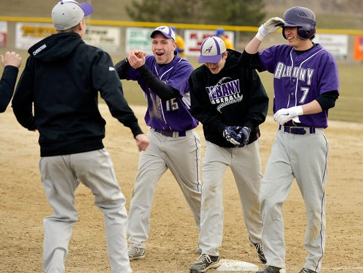Albany players celebrate a game-winning run in the seventh inning against St. Cloud Cathedral Tuesday, April 15 in Avon. Albany won 4-3.