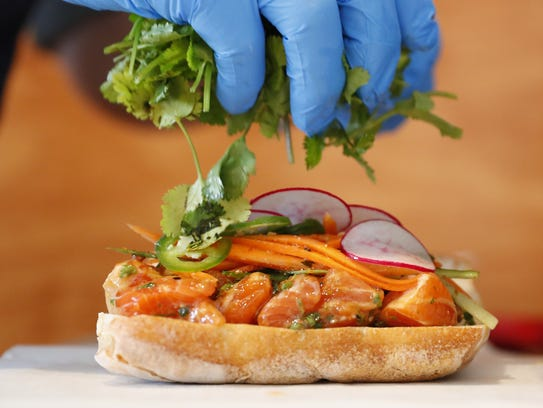 Christopher Nelson prepares a Poke Banh Mi at Nelson's Meat + Fish in Phoenix on April 10, 2018.
