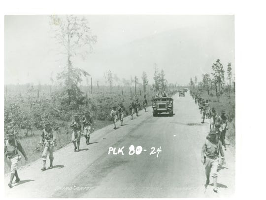"""The """"Red Army"""" infantry marches down a hot, sandy road in the piney woods during the Louisiana Maneuvers."""