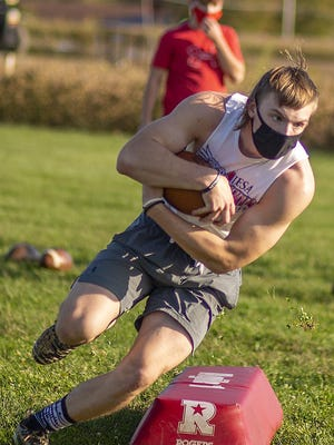 Abingdon-Avon High School junior Leighton Damewood runs the ball during a drill at football workouts on Monday, in Abingdon.