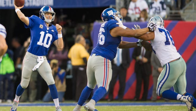 New York Giants quarterback Eli Manning (10) throws a pass in the 2nd quarter as New York Giants offensive tackle Ereck Flowers (76) blocks Cowboys defensive end Greg Hardy (76) at MetLife Stadium.