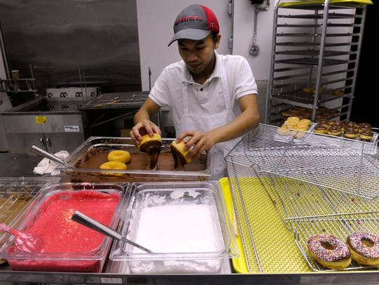 Va San dips doughnuts into chocolate sauce Wednesday morning at Mustang Donuts in Abilene.