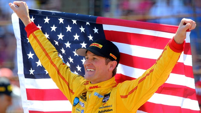 IndyCar Series driver Ryan Hunter-Reay holds an American flag as he celebrates after winning the 2014 Indianapolis 500 at Indianapolis Motor Speedway.