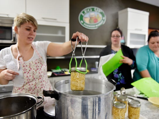 Instructor Alicia Stevens removes sealed jars of chicken