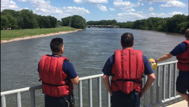 Des Moines firefighters look from a bridge to see if they can spot a man reported in the Des Moines River May 29, 2017.