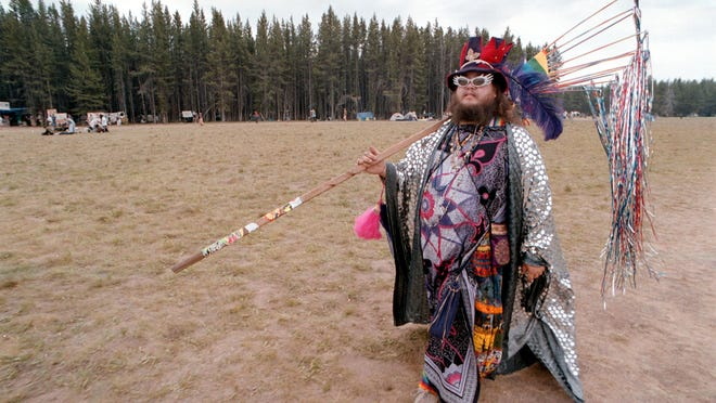 William Walks, who calls himself a wizard, walks across a field during an earlier Rainbow Family Gathering in Idaho. Up to 20,000 members of the Rainbow Family are expected in Mount Tabor in the Green Mountain National Forest this week.