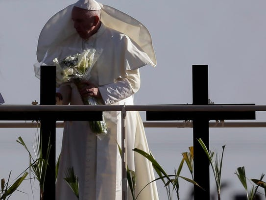 Pope Francis stands on a platform along the banks of