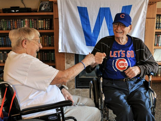 Chicago Cubs fan Ray Styrlund, right, 105, gets a celebratory fist bump from fellow Cubs fan Eleanor Dumolien, 89, before lunch at the Park Vista Thursday, Nov. 3, 2016, in East Moline, Ill. Styrlund said he went to sleep after the Cubs blew their late lead in Game 7 of the World Series on Wednesday night. Dumolien said, as of noon, Thursday she hadn't been to sleep because she was so excited that the Cubs finally won the World Series.