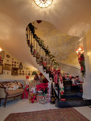 In the entry, poinsettias and garland rope emphasize the drama of the gilded bronze staircase — showcase for a nutcracker collection. Antique dolls are arrayed on the nineteenth-century French canapé. Sconces are from the New York City home of Billy Rose and Fannie Brice.