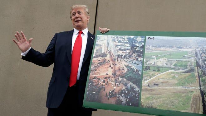 Trump posa frente uno de los prototipos del muro fronterizo, al mismo tiempo que muestra una gráfica en donde se aprecia cómo quedará la obra.