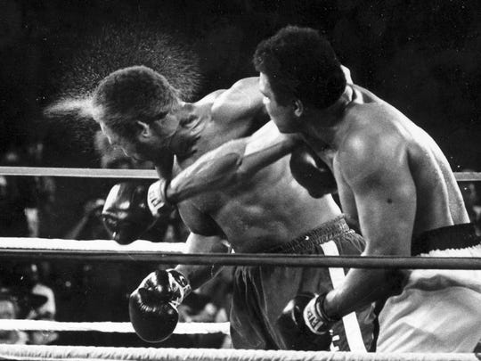This is a Oct. 30, 1974, file photo perspiration flies from the head of George Foreman as he takes a right from challenger Muhammad Ali in the seventh round in Kinshasa, Zaire.