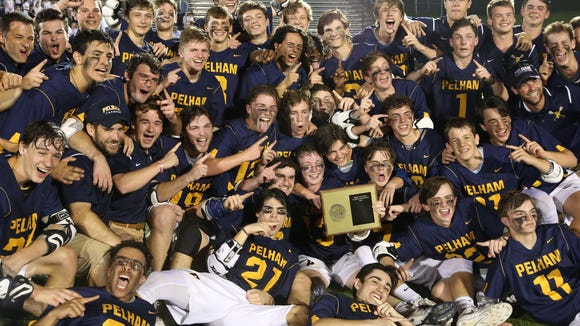 Pelham lacrosse players celebrate with the Section 1 plaque after defeating Rye 9-8 in overtime to win the Class C championship  at Lakeland High School in Shrub Oak May 29, 2018.